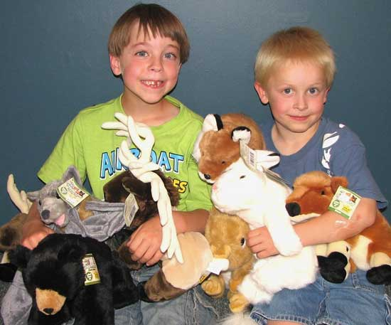Young boys enjoy stuffed wildlife animals.
