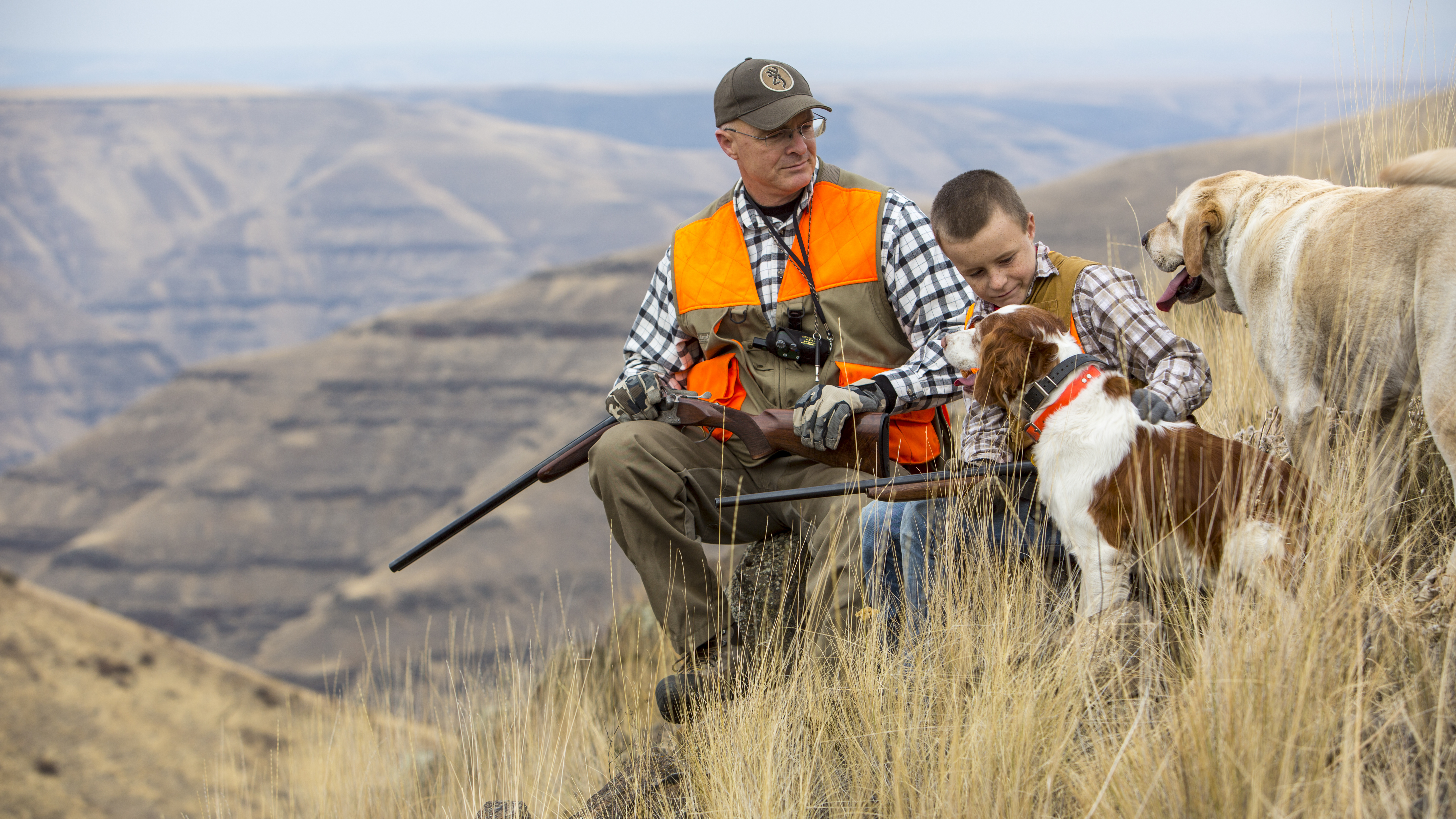 medium shot of a man and boy with their dogs dressed in hunter orange taking a break from hunting October 2015