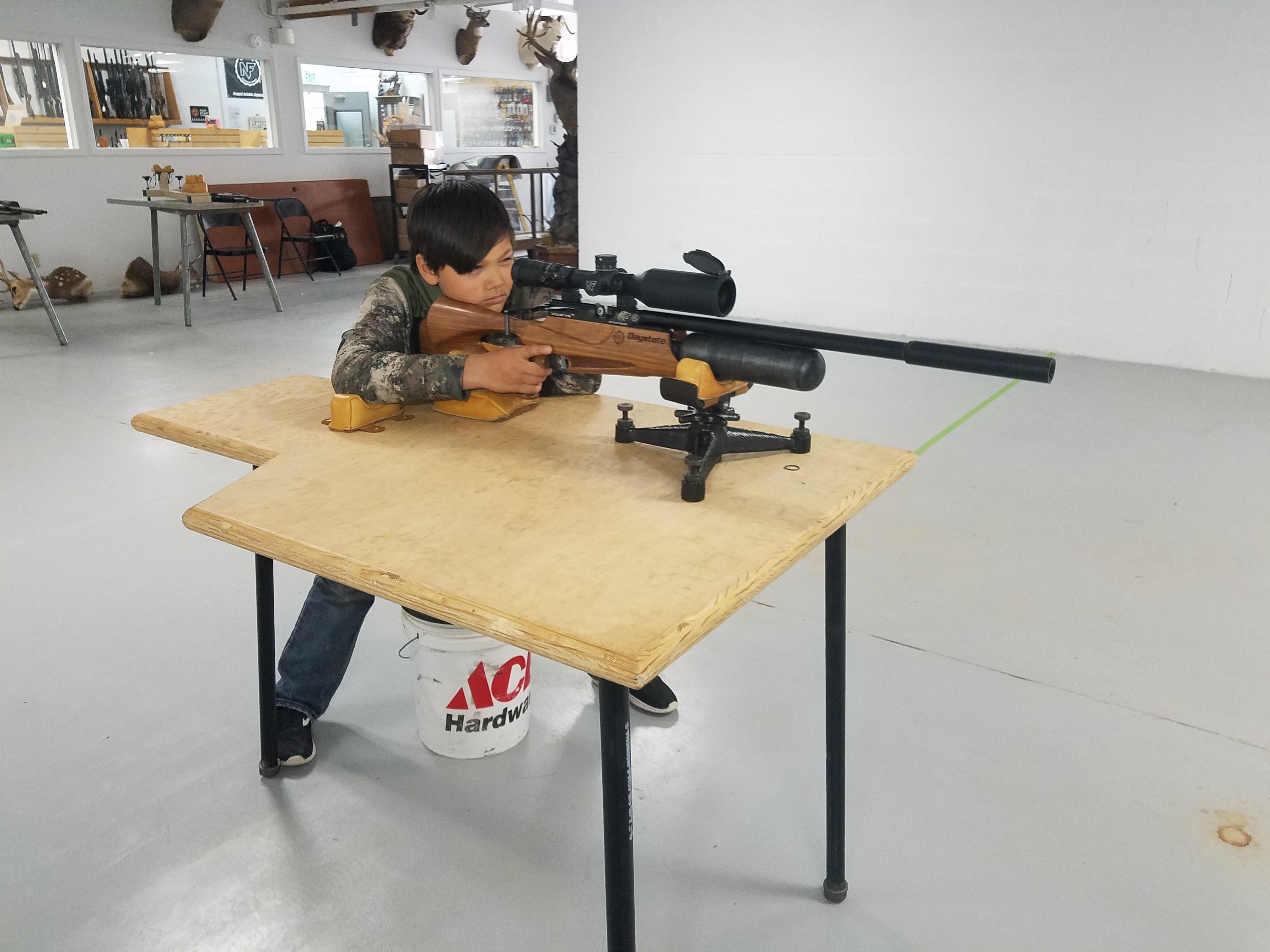 A young shooter is seated at table while he aims an air gun towards a target