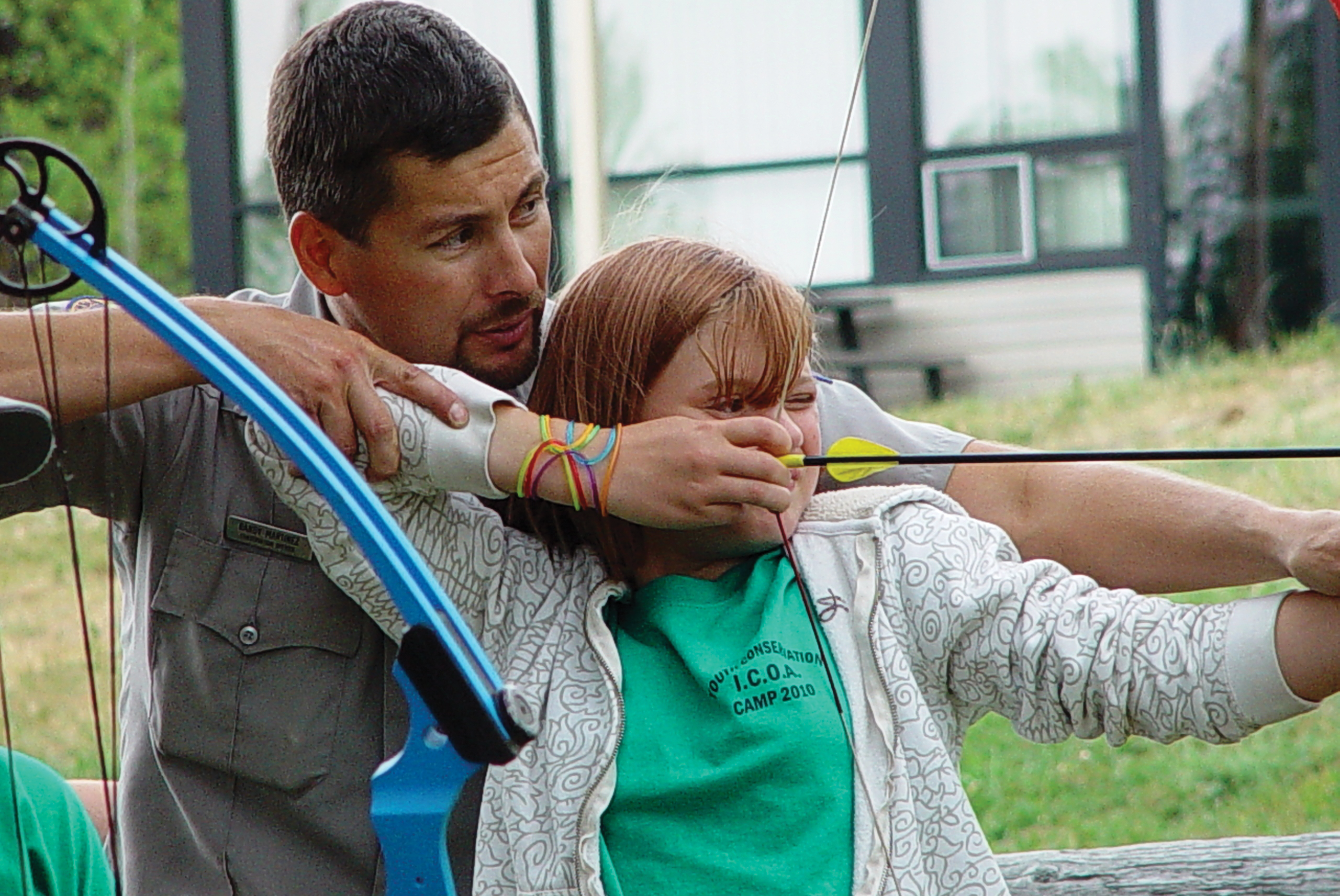 an IDFG  conservation officer shows a girl how to handle a bow and arrow at a hunter education class August 2010