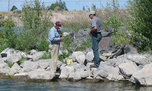 IDFG Conservation Officer checking an anglers fishing license small photo