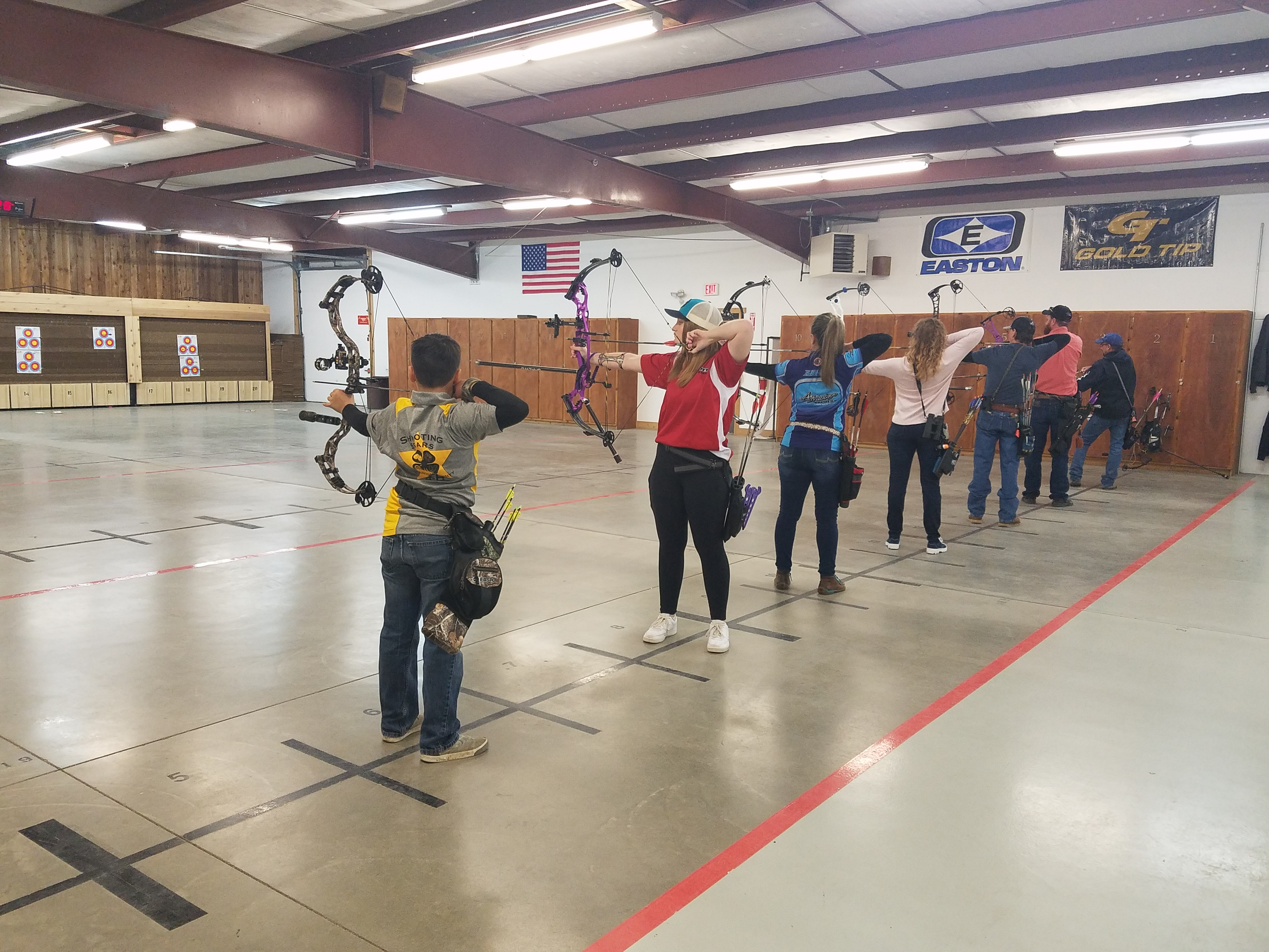 Seven archers draw their bows at the Nampa Public Shooting Range