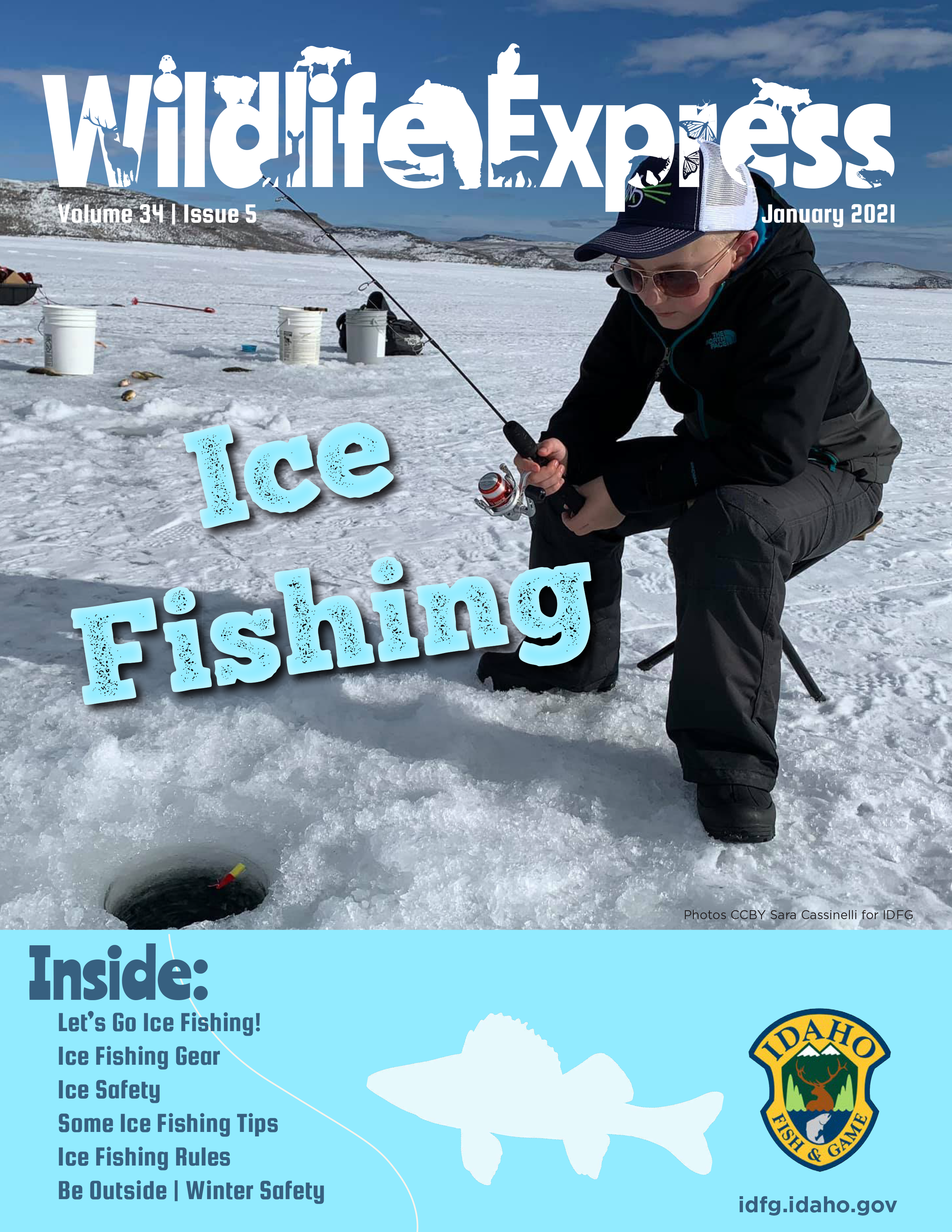 A seated bundled up boy wearing aviator sunglasses holds a fishing pole over an ice fishing hole