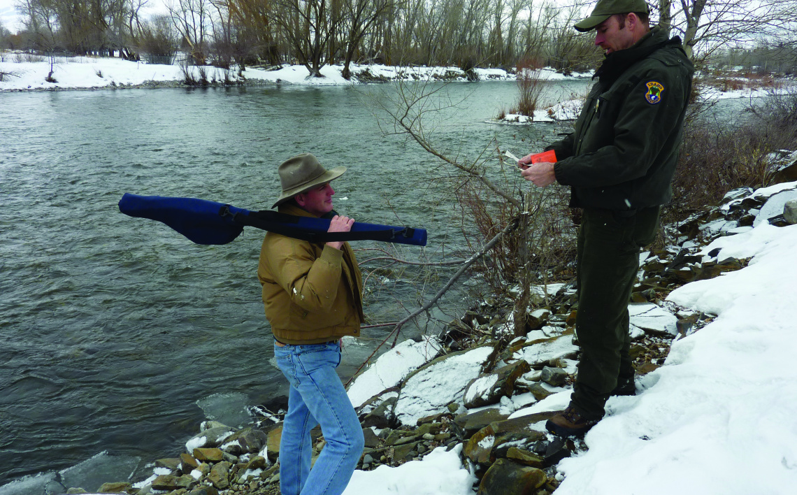 a Fish and Game Conservation officer check an anglers fishing license at the Lemhi Hole Access in Salmon February 2011 in snow