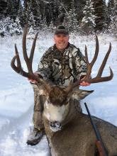 man with his big mule deer buck and rifle in snow vertical shot November 2016