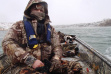 Photo of Duck hunter in boat in cold conditions