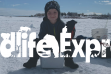 A young boy sits on a cooler on a frozen lake with the words Wildlife Express in the center of the image.