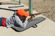 boy wearing a hunter orange cap learning how to fire a rifle during a Hunter Education class August 2016