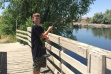 boy fishing from a bridge at Hagerman ponds medium shot June 2015