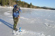 Using a hand auger to drill holes in the ice on Upper Twin Lake