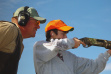 an instructor watches as a boy fires a rifle at a youth pheasant hunt November 2004