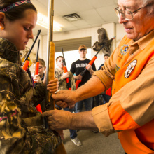 Gary Gillespie shows a girl at Hunter Education class how to use a rifle January 2014