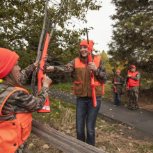 two girls passing rifles over a fence during a hunter education class October 2015