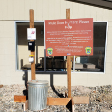 A garbage can next to a large sign with instructions asking mule deer hunters to deposit Chronic Wasting Disease samples in the can.