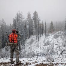 big game hunter dressed in hunter orange using a range finder on a snow coverd mountain ridge Ben Studer medium shot November 2016