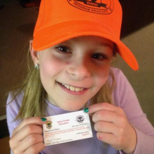 girl with her card after graduating from hunter education wearing a hunter orange cap small photo