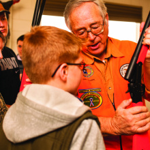 kids learn how to handle a rifle as demonstrated by a hunter education instructor
