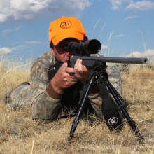 hunter shooter taking aim with his rifle and scope wearing a hunter orange cap April 2014