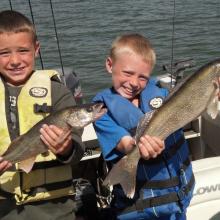 boys in a boat show off their walleye